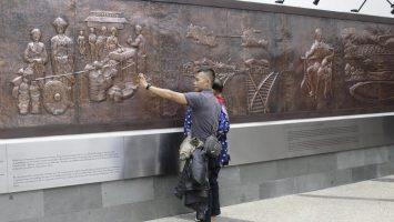 Pengunjung berfoto di relief Taman Sejarah, Jalan Wastukencana, Bandung. Selasa,(28/3/2017). (Septian Setiawan/Magang)